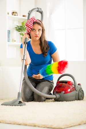 indecision: A young housewife kneeling beside the vacuum cleaner with duster in hand with an expression of indecision on her face thinking where to start cleaning up the house. Stock Photo