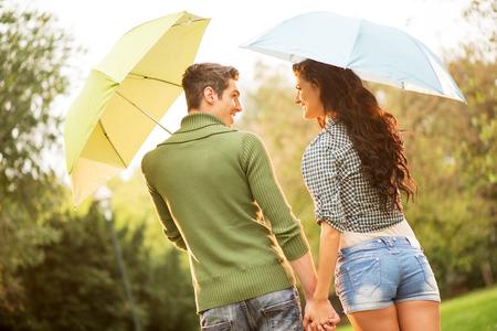 uomo sotto la pioggia: Vista posteriore di una giovane coppia in amore con ombrelloni, mentre a piedi attraverso il parco per mano e guardarsi l'un l'altro con un sorriso. Archivio Fotografico