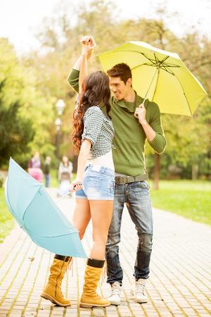 uomo sotto la pioggia: Giovane coppia in amore, ballare nel parco con ombrelloni nelle mani.