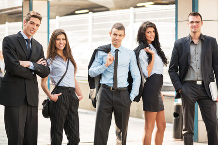 elegantly: Group of young business people elegantly dressed standing outside. Stock Photo