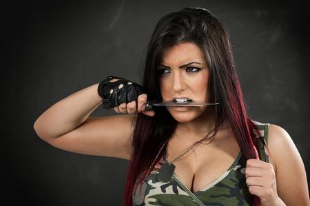 bayonet: Young beautiful military woman holding bayonet in the teeth