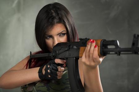 mujer con arma: Hermosa mujer militar joven que sostiene el rifle y apuntar. Preparada para disparar. Foto de archivo