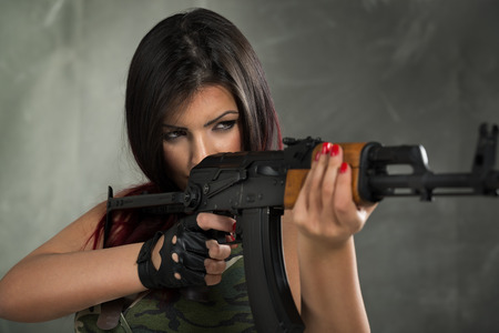 armed: Young beautiful military woman holding rifle and take aim. Ready to shoot.