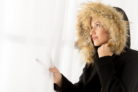 The young beautiful woman, dressed in a jacket with a fur hood, looking through the window.