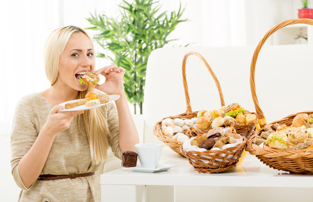 Young pretty blonde woman eating a small sandwich, in the background you can see woven basket with bakery products. With an expression of enjoyment on her face looking at the camera. Stock fotó