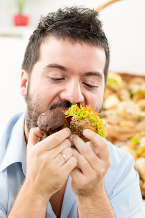 pushed: Close-up of a young man with a beard who greedily pushed into the mouth pastries. In the background is woven basket with pastries.
