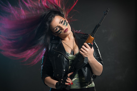 dyed hair: Attractive young woman with disheveled dyed hair is holding an automatic rifle and dangerous expression on her face, painted war paint, looking at the camera.