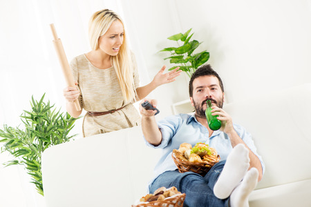 Young man sitting on a couch, holding a bottle of beer in one hand, remote control in the other hand,on the knee had baskets with pastries, while behind him stands a young woman with a rolling pin in hand with an angry expression.