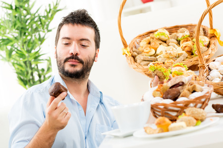 Young man with a beard, holding in his hands a sweet and savory pastries. With a smile looking at delicious bites. In the background you can see woven baskets with pastries. photo