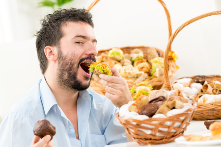Young bearded man eating a small sandwich,with an expression of enjoyment on his face looking at the camera. In the background you can see woven basket with bakery products. photo