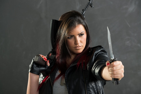 tough girl: A young attractive woman armed with an automatic rifle and a knife standing with outstretched hand holding a knife.