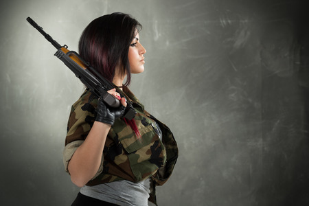 tough girl: Profile of an attractive young women in military camouflage shirt with a rifle in her hand.