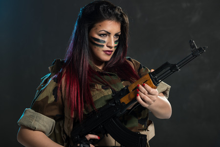 face paint: Attractive young woman with face paint on war paint in uniform holding an automatic rifle.