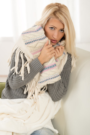 Beautiful blonde girl is sitting on the couch, dressed in a warm wool sweater, tucking at a shawl, with a serious expression on her face looking at the camera.
