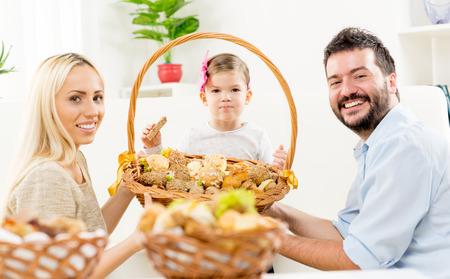 to kneel: Los padres j�venes se arrodillan delante de su peque�a hija, sosteniendo gran cesta tejida con pasteles, y con una sonrisa mirando a la c�mara.