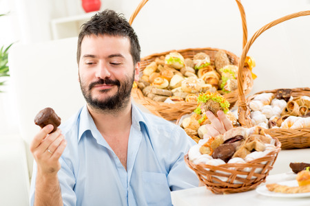 Young man with a beard, holding in his hands a sweet and savory pastries. With a smile looking at sweet cake. In the background you can see woven baskets with pastries. photo