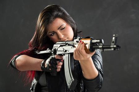tough girl: Attractive girl standing in the attitude of aiming and looking through the sight automatic rifle. Stock Photo