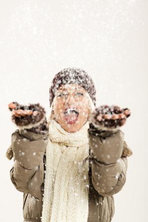 ropa de invierno: Chica alegre joven en ropa de invierno con las manos extendidas capturas copos de nieve, regocij�ndose en la primera nieve.