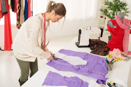 m�quina de coser: Mujer hermosa joven con cinta m�trica sobre el cuello, corte con tijeras de material de patr�n de costura. En la mesa de al lado del material es una m�quina de coser y el maniqu�.