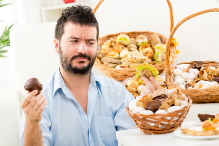 Young man with a beard, holding in his hands a sweet and savory pastries in which looking, wondering who to choose. In the background you can see woven baskets with pastries. photo