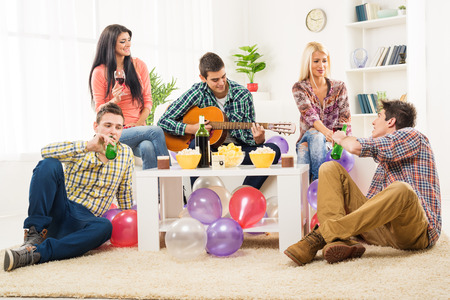 Small group of young people at the home party, enjoy the sounds of the acoustic guitar, drinking wine and beer.