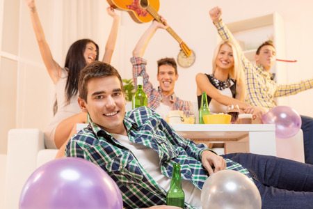 Young guy at house party, lying on the floor, smiling, looking at the camera  photo