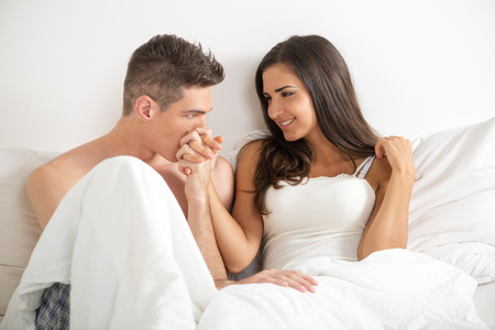 Young heterosexual couple in bed. Handsome guy holding his pretty girlfriend's hand and kissing her hand. Archivio Fotografico