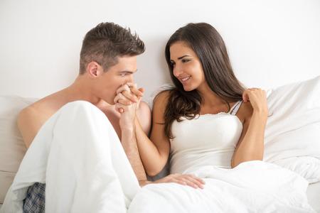 esposas: Pareja heterosexual joven en la cama. Chico guapo sosteniendo la mano de su novia bonita y bes�ndole la mano. Foto de archivo