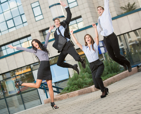 people in office: Group of young cheerful business people in front of office building, photographed at the moment of the jump.