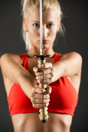 Pretty blonde girl in a sports bra, holding in her outstretched hands katana, which is in the foreground, with a serious expression on her face looking at the camera.