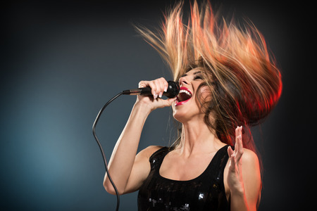 A young woman rock singer with tousled long hair holding a microphone with stand and sing with a wide open mouth.