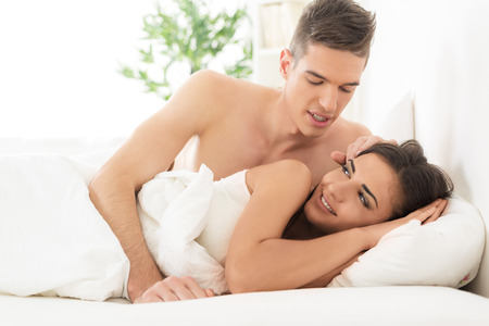 stroking: Young couple in bed, handsome boy wakes his pretty girl stroking her hair.