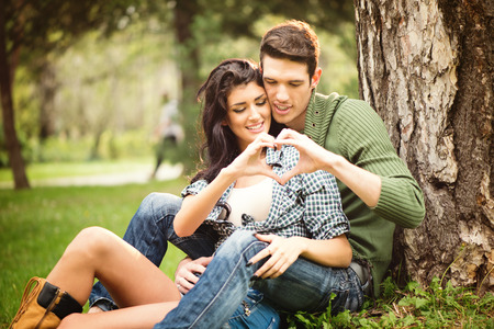 Young heterosexual couple sitting on the grass in the park next to the tree and touching with the fingers forming a heart shape. photo