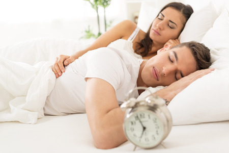 bed time: Young heterosexual couple sleeping in bed next to an alarm clock.
