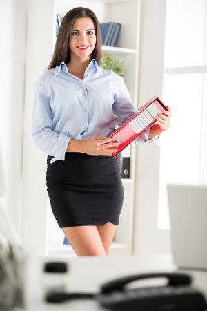 minifalda: Joven mujer de negocios bonita en una falda corta, la celebración de una carpeta y con una sonrisa mirando a la cámara.