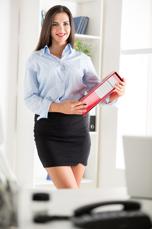 Young pretty business woman in a short skirt, holding a binder and with a smile looking at the camera.