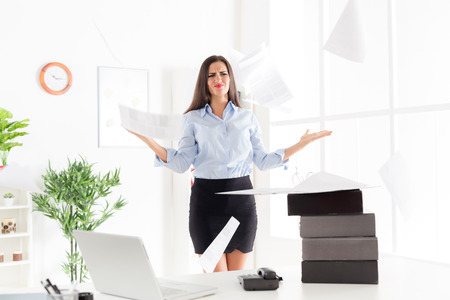 office physical pressure paper: Young businesswoman standing in office, next to a table on which are stacked binders and with an expression of discontent on her face throwing papers from the binder. Stock Photo