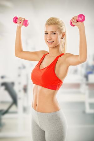 pesas: La muchacha bonita joven rubia en ropa deportiva en el gimnasio, de pie con los brazos levantados en el que sostiene pesas y con una sonrisa mirando a la c�mara.