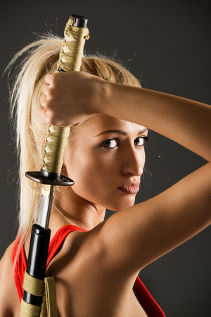 challenging sex: Profile of beautiful young blond woman who draws a katana behind back and with a serious expression on her face looking at the camera.