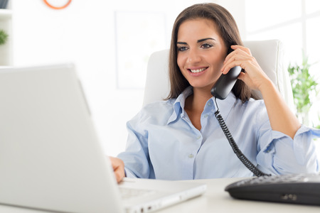 Young business woman phoning in office, sitting at an office desk in front of laptop, in which looks with a smile on her face.