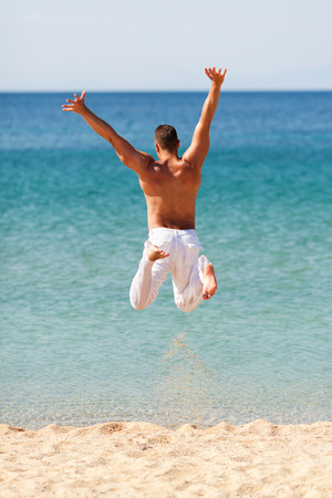 white pants: Happy young man in white pants jumping into water