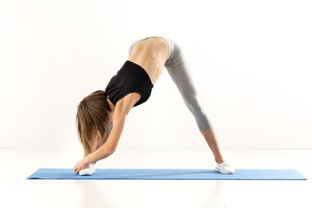 jambes �cart�es: Jeune, sportif construit fille de faire des exercices d'�tirement. Debout, les jambes �cart�es sur le tapis d'exercice, courb� vers le sol.