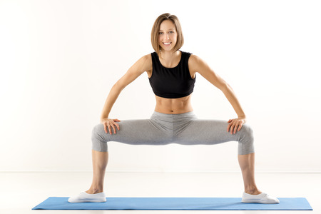 knees bent: Athletic built woman in sports clothes, standing on the mat for exercise, in a sitting position with her legs bent at the knees. With a smile looking at the camera.