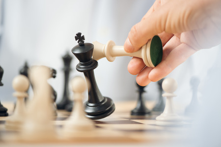 Close-up of human hand holding a white chess king over the chessboard, while crashes black chess king.