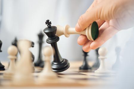 conflicto: Primer plano de una mano humana que sostiene un rey de ajedrez blanco sobre el tablero de ajedrez, mientras que bloquea rey de ajedrez negro. Foto de archivo