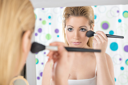 Close-up of beautiful girl with blue eyes applying blush in front of mirror in his bathroom in the morning. Rear view. photo