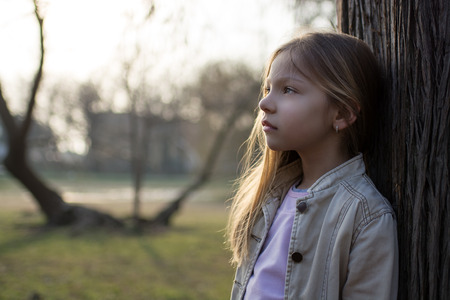 conceived: Little girl in the park, leaning against a tree, and conceived looks into the distance. Stock Photo