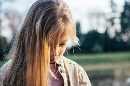 girl portrait: Close-up of a little girl with long hair, standing alone, head bowed, looking down with a sad expression on her face.