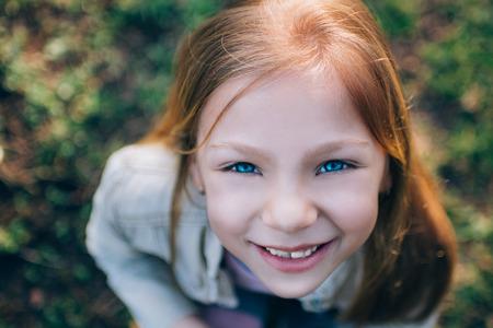 jolie petite fille: Close-up le visage de petite fille avec un sourire et de beaux yeux bleus regardant la cam�ra. Photographi� par le haut