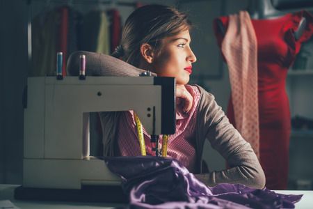 people sewing: Beautiful tired woman sits in front of the sewing machine and thinking. Vintage concept. Stock Photo
